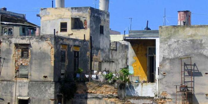although the building is crumbling, the yellow door and laundry show it is someone's Havana home